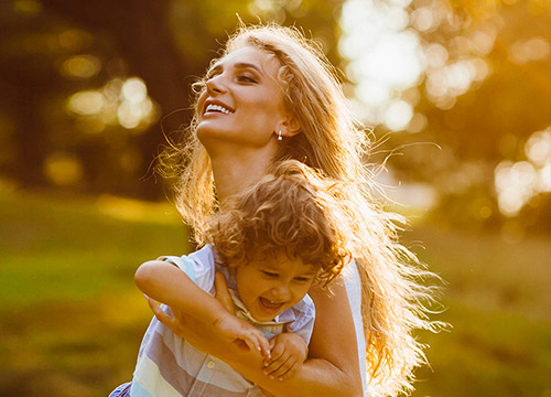 Femme portant un enfant et souriant